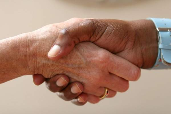 Helping hand shakes another in an agreement
